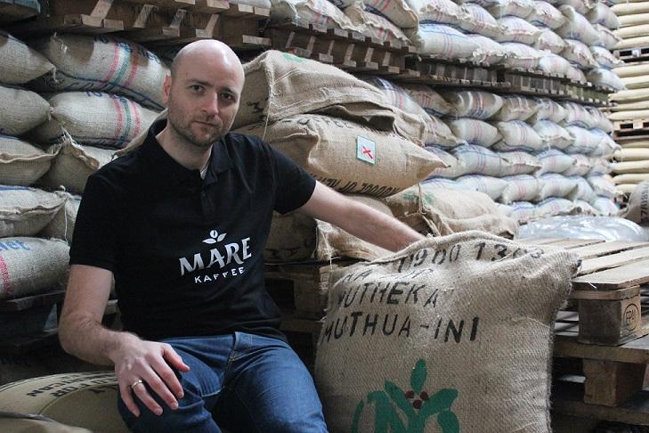 Marc Rode von Mare Kaffee neben einem Kaffeesack aus Muthuaini im Kaffeelager