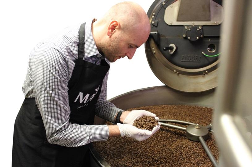 Marc Rode von Mare Kaffee bei der Qualitätsprüfung an der Röstmaschine